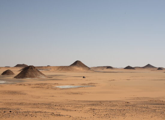Small vehicle far away in sight in the middle of the northern african Sahara region