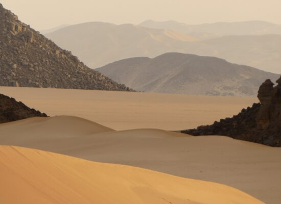 Wonderful view of black rock and red dunes in the Sahara