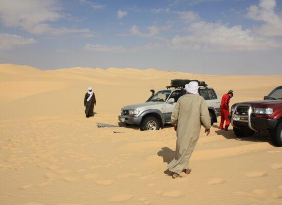 Alle helfen zusammen die Fahrzeuge aus dem Weichsandfeld zu befreien in der Sahara auf einer Expedition mit Outback Expeditions off the beaten track Westafrika Expedition Mauretanien