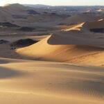Rötlicher Sand der Dünen wird immer wieder von schwarzem Fels durchbrochen