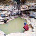 2 Tuareg sitzen an einem Wasserloch im Fels der Sahara